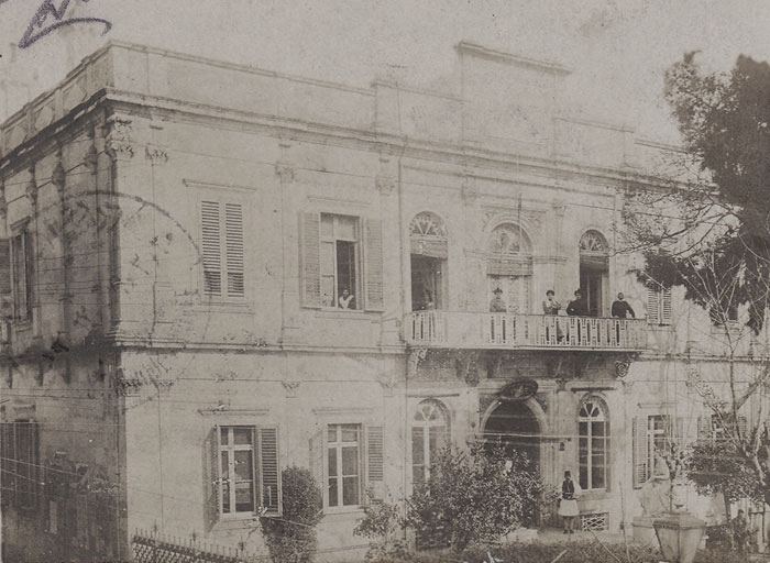 A photocard from the the early 20th century with what looks like the house of a prominent Turkish official, complete with the seal of the Sultan above the front door.